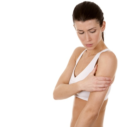 injured woman: beautiful brunette is having a pain in her shoulder