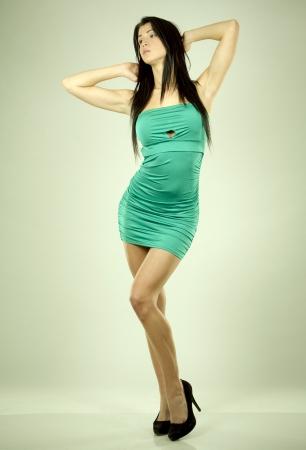 pretty brunette wearing green dress on light background Stock Photo - 18468163