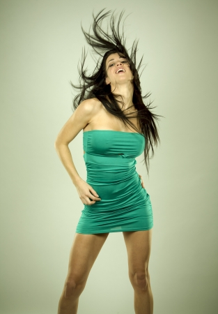 pretty brunette wearing green dress on light background Stock Photo - 18468179