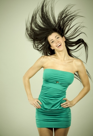 pretty brunette wearing green dress on light background Stock Photo - 18468180