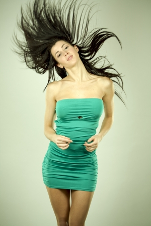 pretty brunette wearing green dress on light background Stock Photo - 18468181