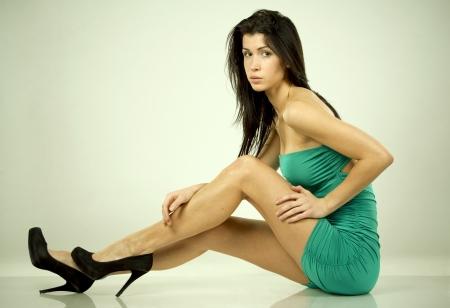 pretty brunette wearing green dress on light background Stock Photo - 18453240