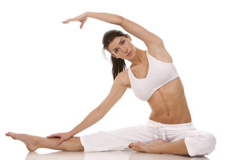 растягивание: Красивая брюнетка в белой спортивной одежды на белом фоне