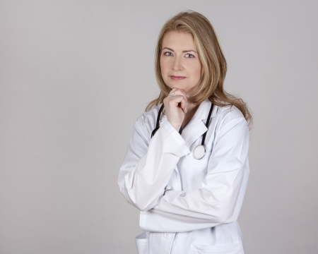 blond female doctor posing on light grey background photo
