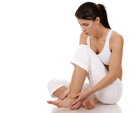 adult's feet: brunette holding her feet on white isolated background