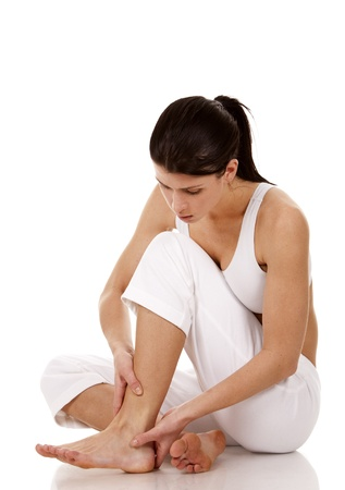 wound care: brunette holding her feet on white isolated background