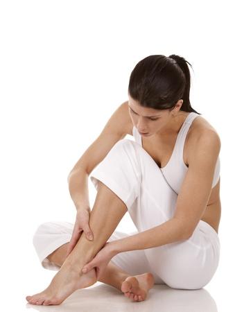 tenendo bruna suoi piedi su sfondo bianco isolato