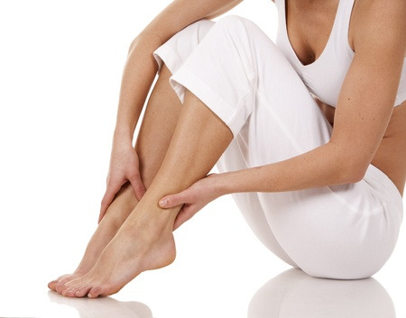 woman legs: brunette holding her feet on white isolated background
