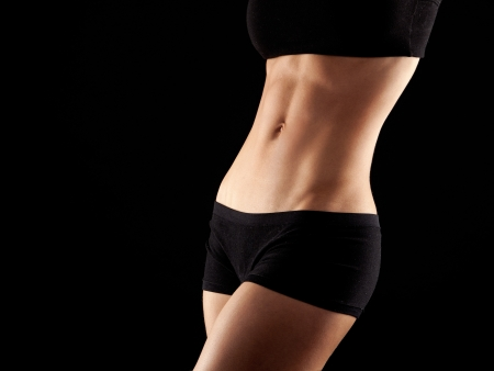 body curve: female fitness model posing on black background