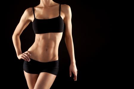 forme: Modèle de fitness femme posant sur fond noir Banque d'images