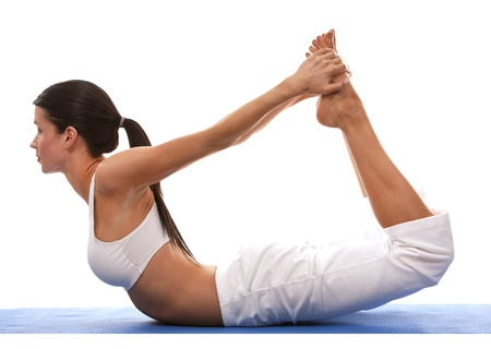 pretty brunette is exercising yoga on white background photo