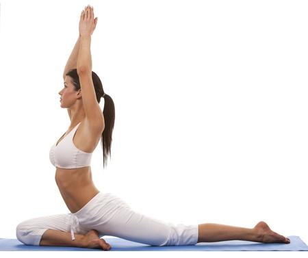 pretty brunette is exercising yoga on white background photo