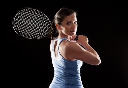 brunette playing tennis on black background Stock Photo - 19907597