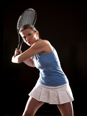 brunette playing tennis on black background Stock Photo - 19907569
