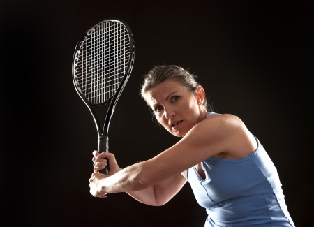 brunette playing tennis on black background Stock Photo - 19907570