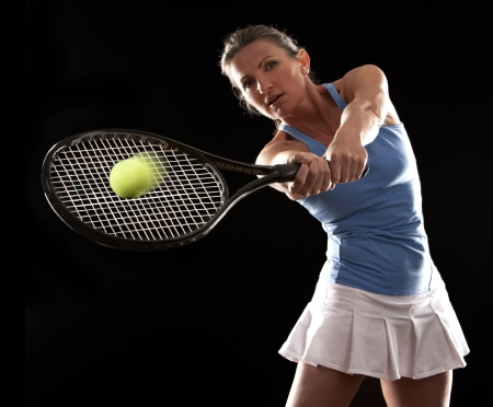 brunette playing tennis on black background Stock Photo - 19907590