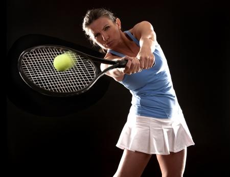 raqueta de tenis: Morena jugando tenis sobre fondo negro Foto de archivo