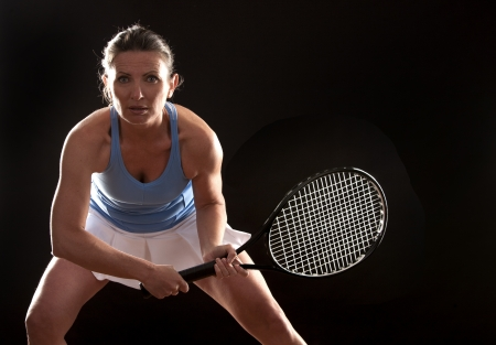 brunette playing tennis on black background Stock Photo - 19907600