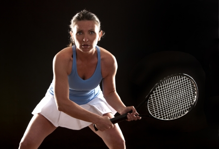 brunette playing tennis on black background photo