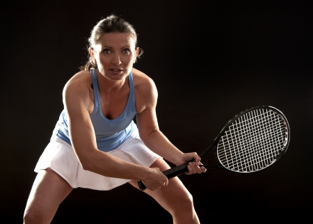 brunette playing tennis on black background Stock Photo - 19907571