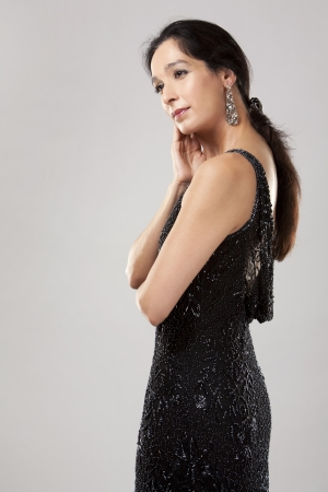 beautiful woman in her 40s wearing black evening dress on light background Stock Photo - 20603689