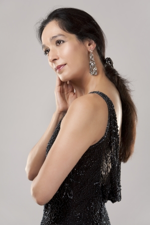 beautiful woman in her 40s wearing black evening dress on light background Stock Photo - 20603710