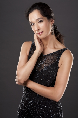 beautiful woman in her 40s wearing black evening dress on light background Stock Photo - 20603708