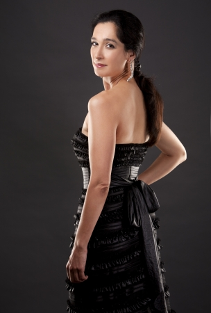 beautiful woman in her 40s wearing black evening dress on light background Stock Photo - 20603749