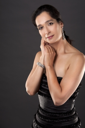 beautiful woman in her 40s wearing black evening dress on light background Stock Photo - 20603712