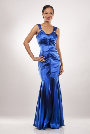 beautiful woman wearing blue evening dress on light background