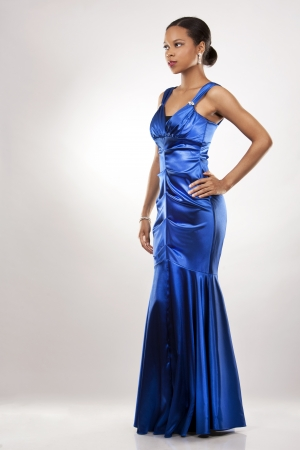 evening gown: beautiful woman wearing blue evening dress on light background