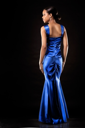 beautiful woman wearing blue evening dress on black background Stock Photo - 20787391