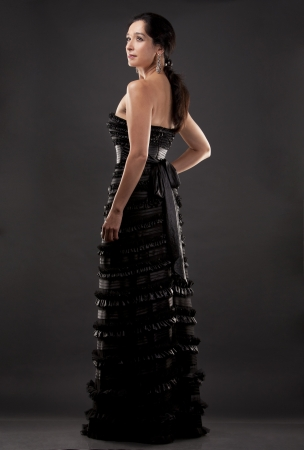 beautiful woman in her 40s wearing black evening dress on dark background Stock Photo - 21172555