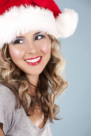 pretty blond wearing christmas hat on light blue background photo