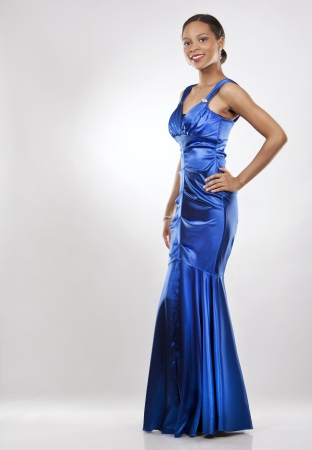 evening gowns: beautiful woman wearing blue evening dress on light background