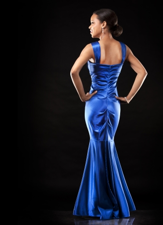 beautiful woman wearing blue evening dress on black background