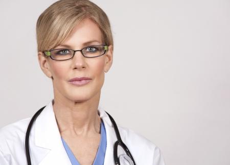 beautiful mature doctor wearing scrubs on light background photo