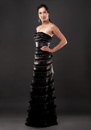 beautiful woman in her 40s wearing black evening dress on dark background