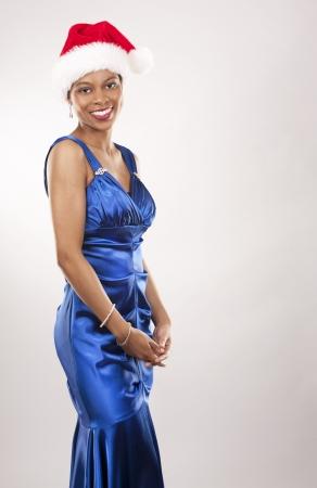 beautiful woman wearing blue evening dress and Christmas hat Stock Photo - 22172745