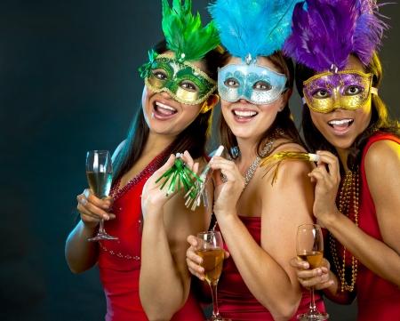 indian mask: beautiful three women having fun during party on dark background