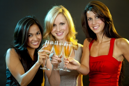 beautiful three women having fun during party on dark background photo