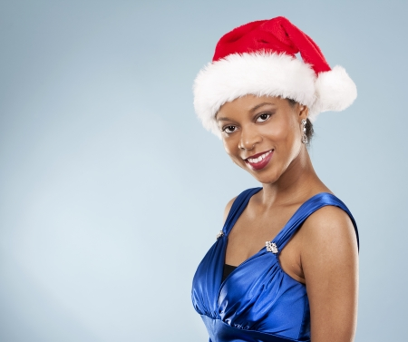 beautiful woman wearing blue evening dress and Christmas hat Stock Photo - 22361739