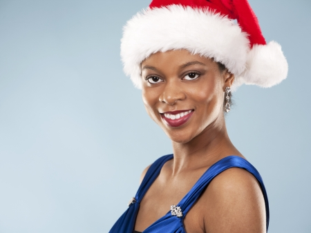 beautiful woman wearing blue evening dress and Christmas hat Stock Photo - 22361740