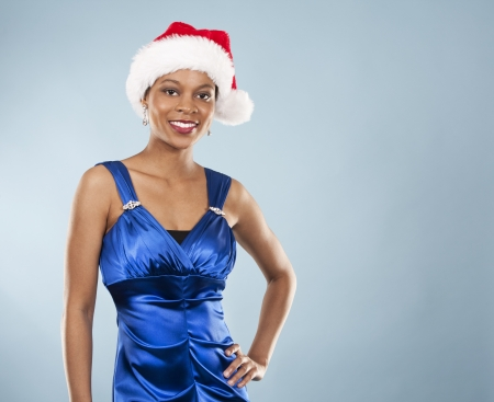 beautiful woman wearing blue evening dress and Christmas hat photo