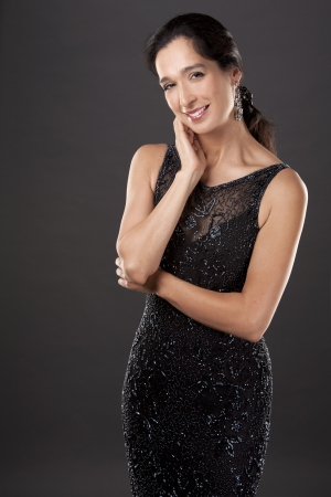 beautiful woman in her 40s wearing black evening dress on light background photo