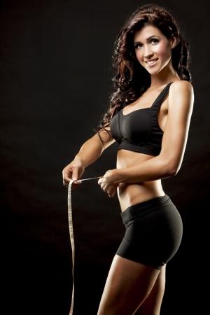 fitness model brunette measuring waist on black background