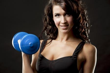 fitness model brunette holding weights on black background
