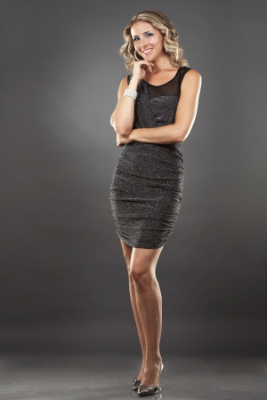 pretty blond wear dress on dark grey background photo