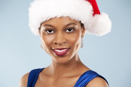 beautiful woman wearing blue evening dress and Christmas hat Stock Photo - 22736404