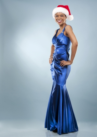 beautiful woman wearing blue evening dress and Christmas hat Stock Photo - 22736406
